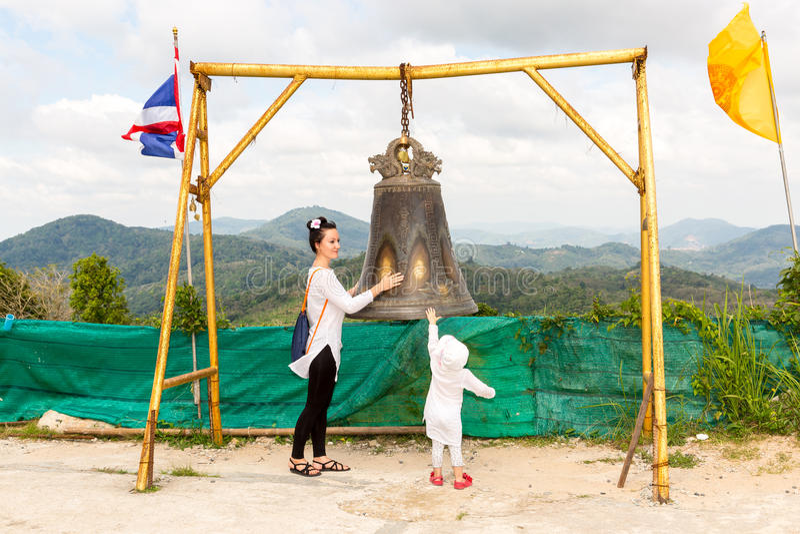 孩子和妈妈在泰国锣附近在普吉岛 在佛教寺庙的传统亚洲响铃在泰国 在金子菩萨附近的著名大响铃愿望 图库摄影