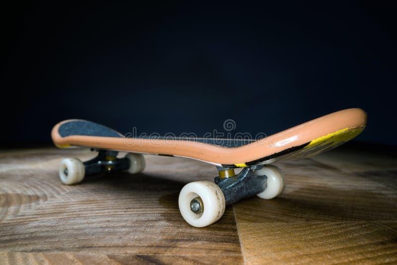 ?? 孩子和少年的一个小滑板能使用与手手指 青年文化,极限运动 库存图片