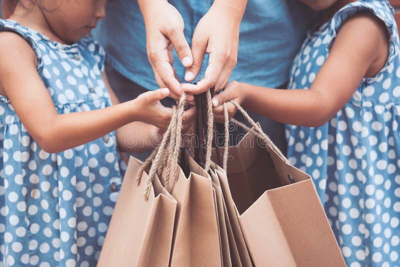 孩子和父母帮助对拿着购物袋 免版税库存照片