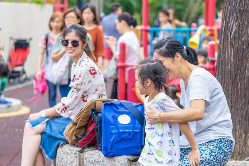 孩子和父母有美好时光在九龙公园操场 免版税库存照片