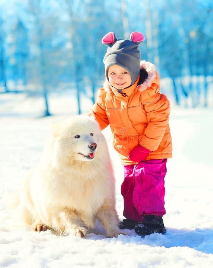 孩子和白色萨莫耶特人狗在雪冬日 库存照片