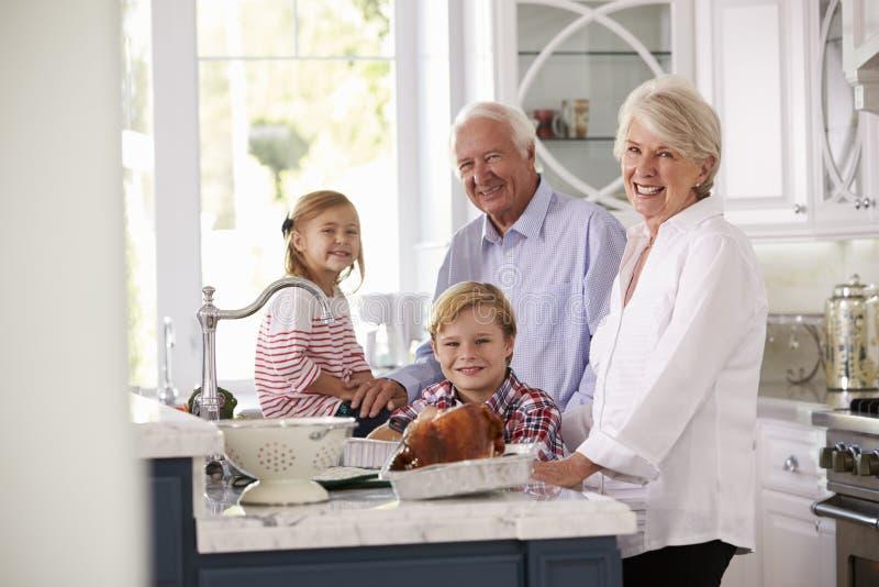 孩子和祖父母在厨房里做烘烤土耳其膳食 免版税库存图片