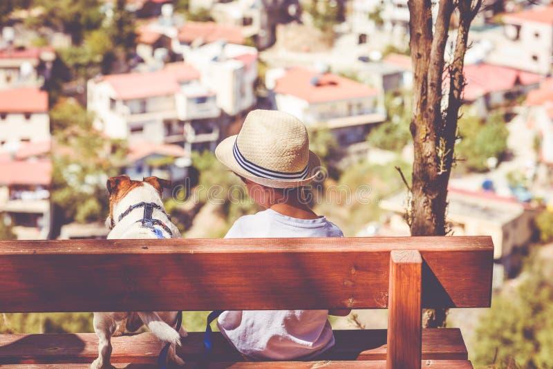 孩子和精力充沛的活跃狗坐长凳在宠物友好的公园在看下来村庄的山顶部 库存图片
