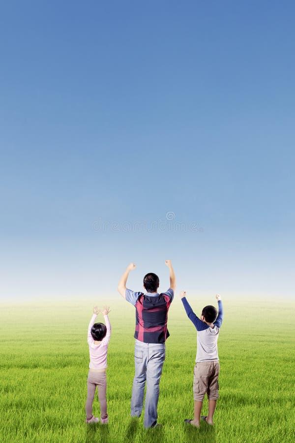 孩子和他们的父亲举手在领域 库存照片