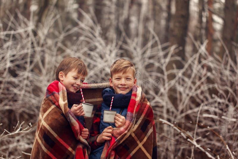孩子喝巧克力热饮在温暖的毯子下在冬天森林圣诞节假期 库存照片