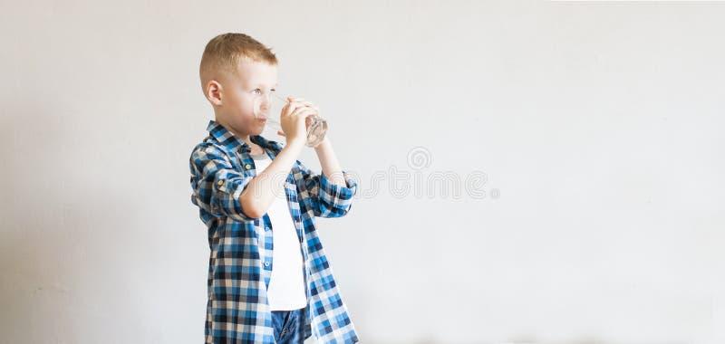 孩子喝纯净的水 免版税库存照片