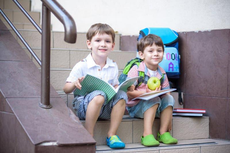 孩子回到学校 新的学年开始在暑假以后 有背包和书的两个男朋友在第一schoo 免版税库存照片