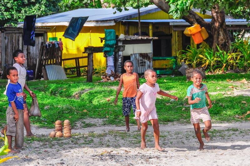 孩子在一个地方村庄在马娜海岛,斐济 免版税库存图片