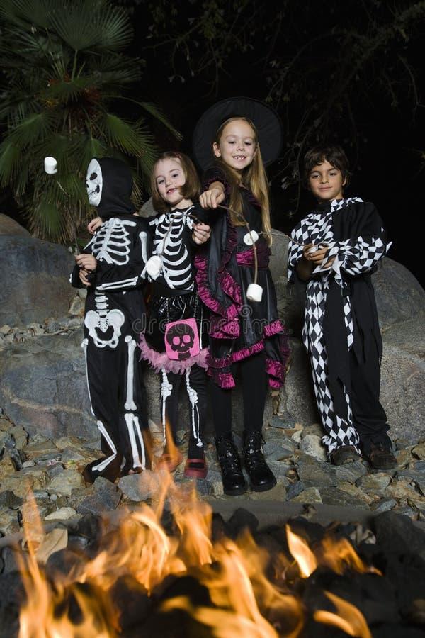 孩子在万圣夜打扮烹调在营火的蛋白软糖 免版税图库摄影
