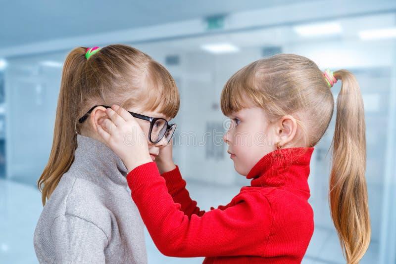 孩子在他的双姐妹上把玻璃放 免版税库存图片