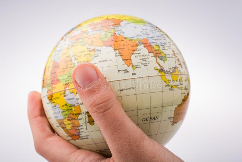 孩子在他的手上的拿着地球 图库摄影