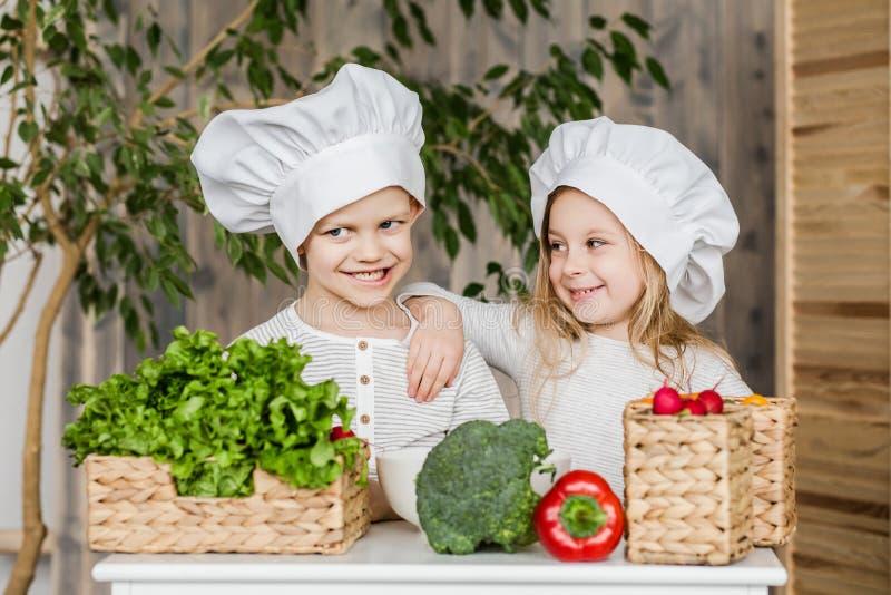 孩子在做菜沙拉的厨房里 健康的食物 菜 家庭 免版税库存照片