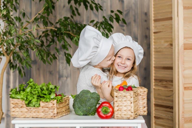 孩子在做菜沙拉的厨房里 健康的食物 菜 家庭 图库摄影