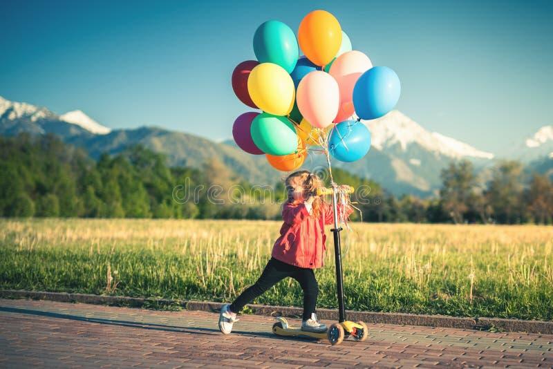 孩子在公园学会乘坐滑行车在晴朗的夏日 学龄前儿童男孩和女孩乘坐路辗的安全帽的 图库摄影