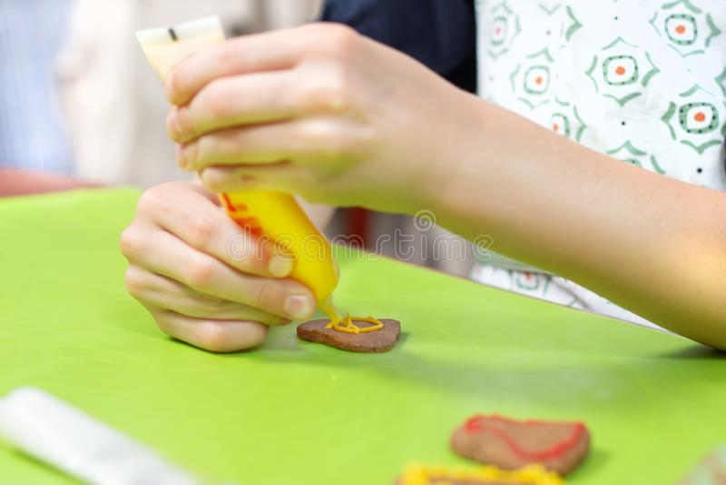孩子在厨房里 装饰与五颜六色的结冰的曲奇饼 儿童的手在黄色紧压结霜 库存图片