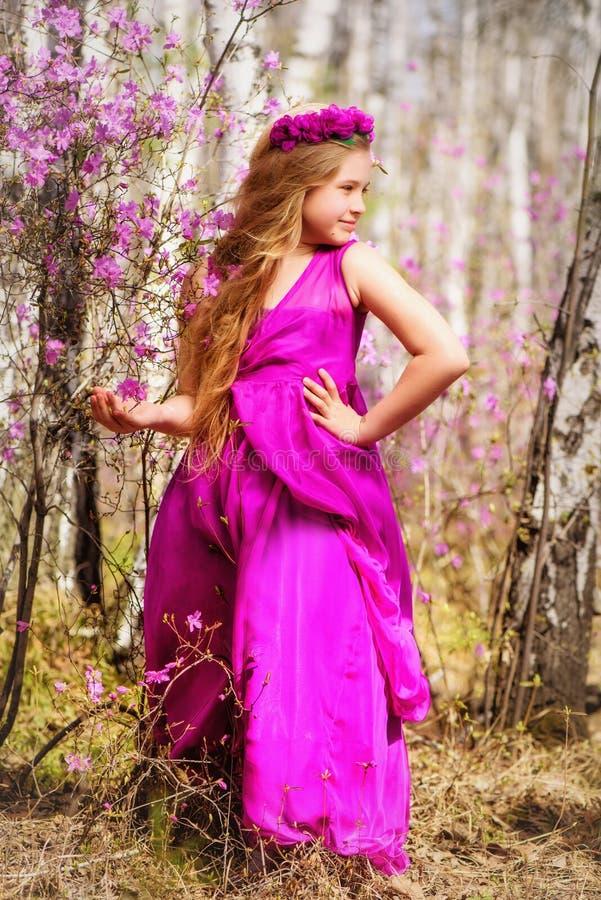 孩子在喇叭茶和桦树中站立在一桃红色礼服和微笑 库存照片