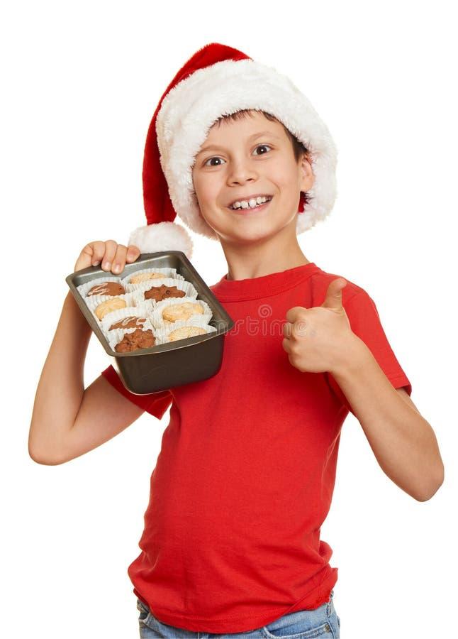孩子在圣诞老人帽子穿戴了用在白色背景隔绝的曲奇饼 除夕和寒假概念 库存图片