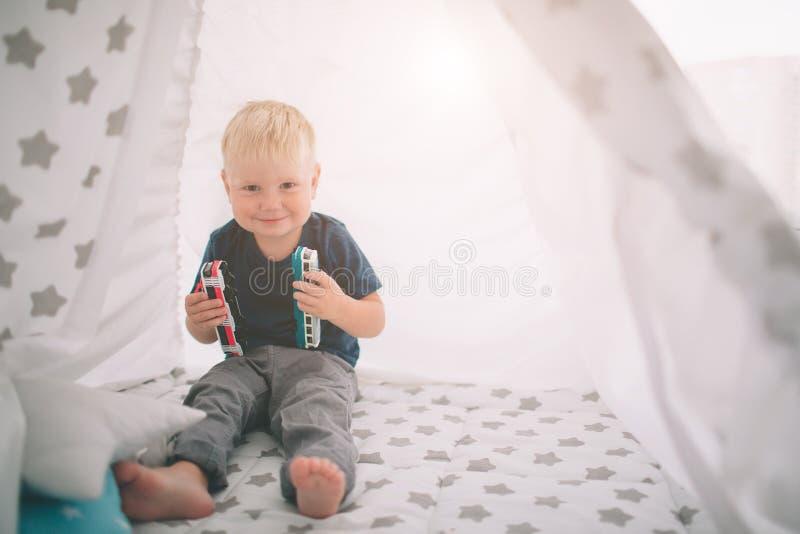孩子在地板放置 男孩在家充当有玩具汽车的家早晨 偶然生活方式在卧室 库存照片