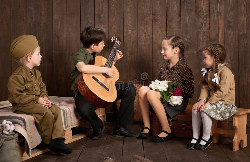 孩子在坐和弹吉他的减速火箭的军服打扮,派遣战士到军队,黑暗的木背景, r 免版税库存图片