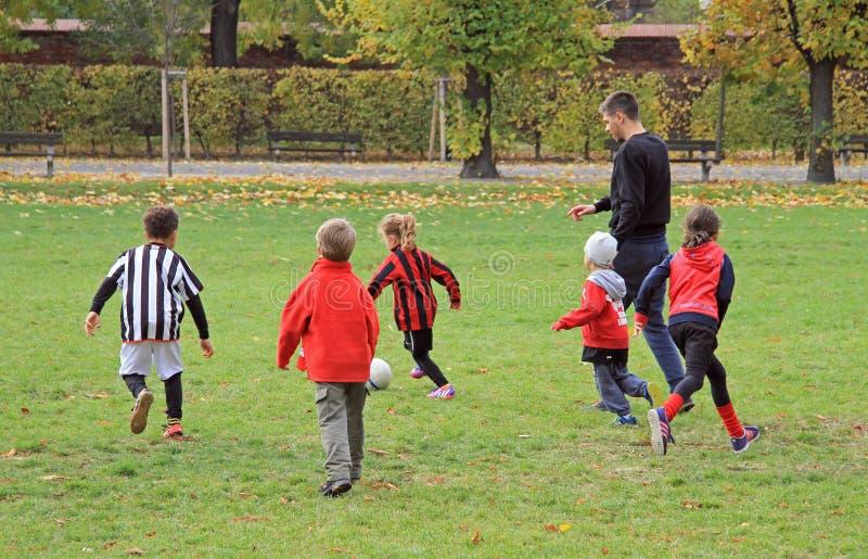 孩子在城市公园踢橄榄球 免版税图库摄影