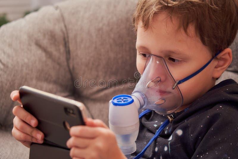 孩子在家做吸入雾化器 在面孔佩带吸入蒸气的面具雾化器喷洒了疗程入肺  免版税库存照片