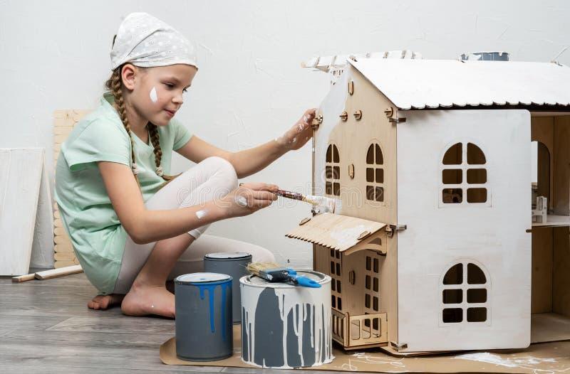 孩子在工作:女孩整洁地绘小家家的门面有小缨子的在白色 免版税库存图片