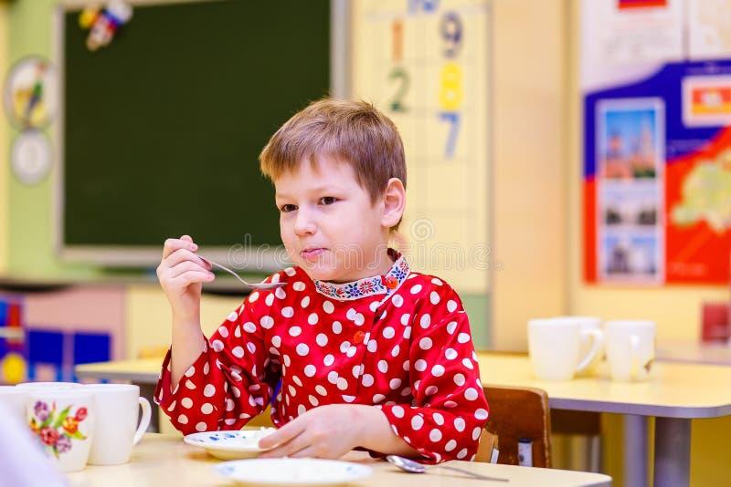 孩子在幼儿园吃粥 库存照片