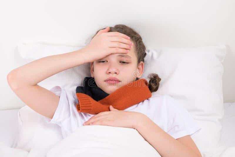 孩子在床上握在他前额减少的一只手 免版税图库摄影