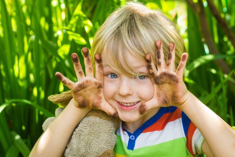 孩子在庭院里用肮脏的手 免版税库存图片