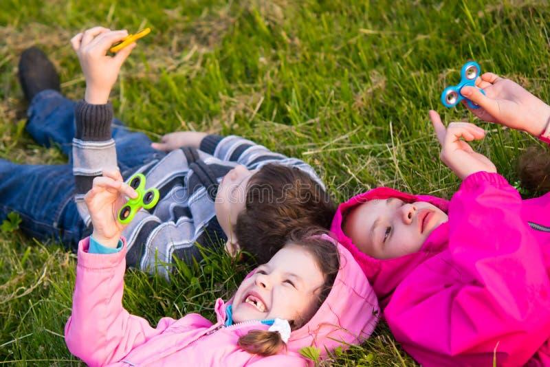 孩子在微笑和使用在锭床工人的草说谎 库存图片