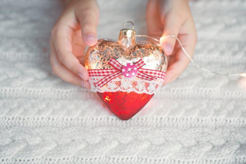 孩子在手上拿着玻璃心脏,圣诞节玩具-一本诗歌选在一件温暖的被编织的毛线衣的背景 晚上时间 免版税库存照片