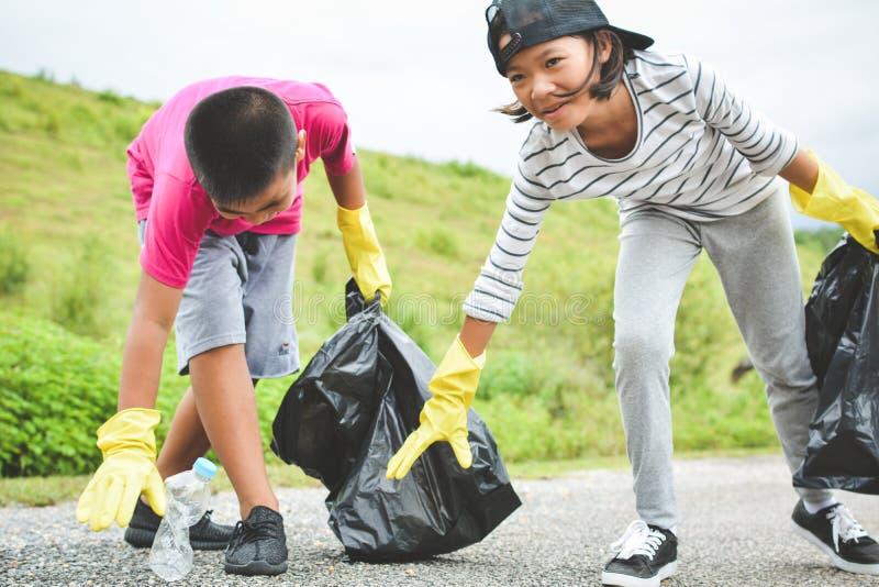 孩子在拾起空瓶塑料的黄色手套递入容器袋子 免版税图库摄影