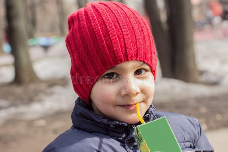 孩子在操场喝汁液 情感特写镜头画象 免版税图库摄影