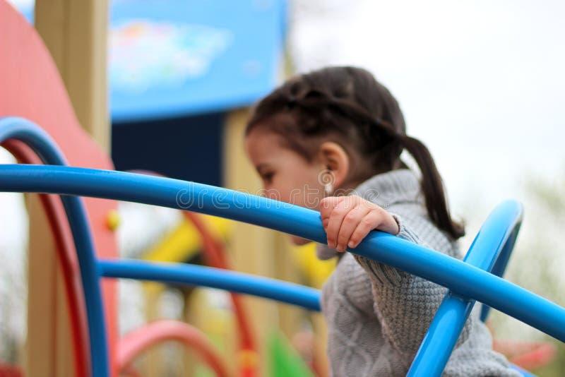 孩子在操场攀登管子的蓝色被焊接的建筑 免版税库存图片