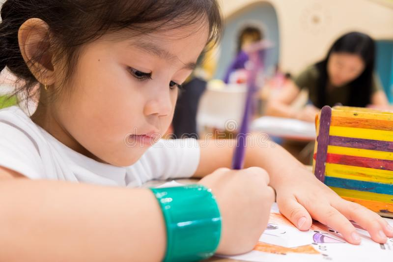 孩子在教室绘与颜色铅笔的画有他们的老师的学会油漆技巧 他们是实践 免版税库存照片