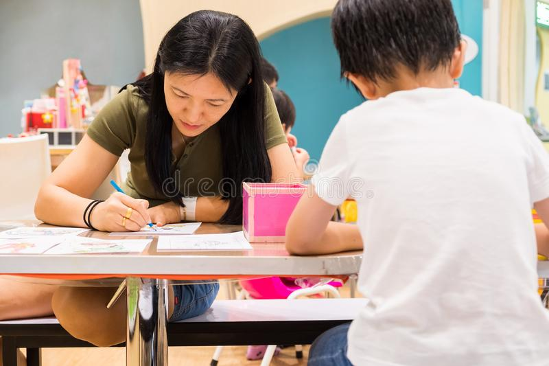 孩子在教室绘与颜色铅笔的画有他们的老师的学会油漆技巧 他们是实践 免版税图库摄影