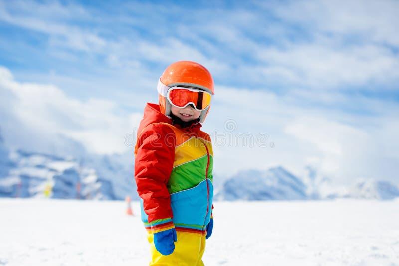 孩子在有不可思议的地毯进来下坡在山的推力和五颜六色的训练锥体的高山滑雪学校在一个晴朗的冬天 库存图片