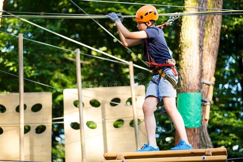 孩子在森林冒险公园 在橙色盔甲的孩子和在高绳索足迹的蓝色T恤杉攀登 敏捷性技能 免版税库存图片