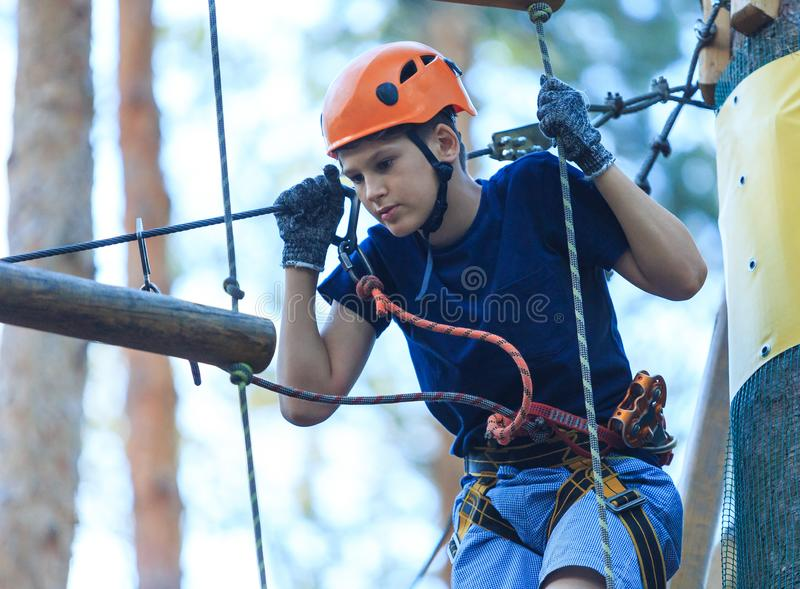 孩子在森林冒险公园 在橙色盔甲的孩子和在高绳索足迹的蓝色T恤杉攀登 免版税图库摄影