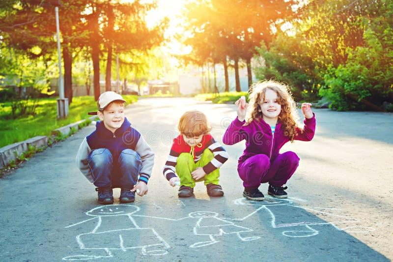 孩子在沥青画在夏天公园 免版税库存照片