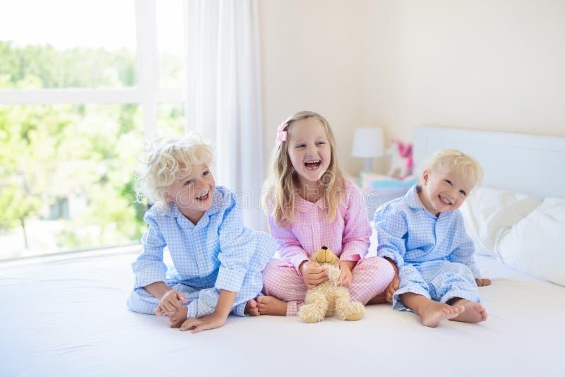 孩子在河床上 睡衣的孩子 家庭卧室 免版税库存图片