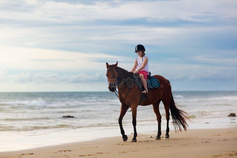 孩子在海滩的骑乘马 孩子骑马 免版税图库摄影