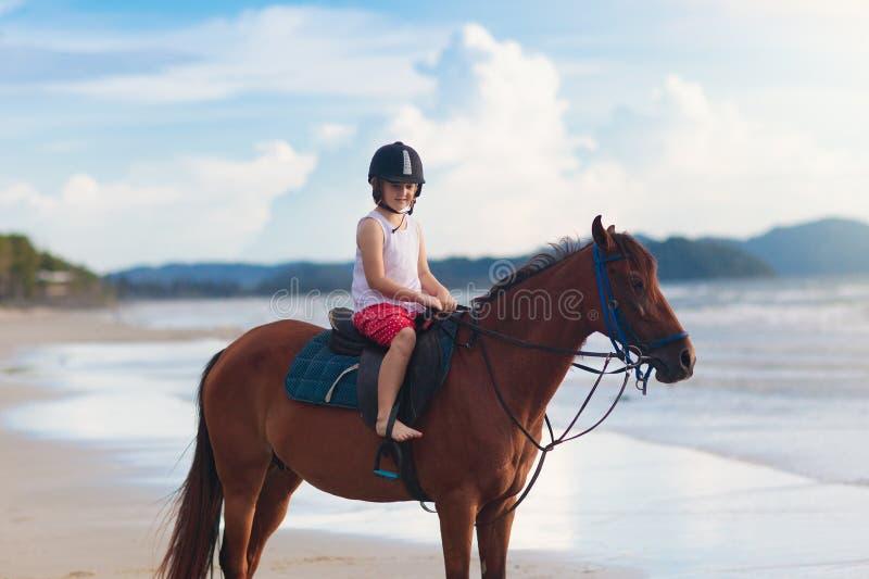 孩子在海滩的骑乘马 孩子骑马 免版税库存图片