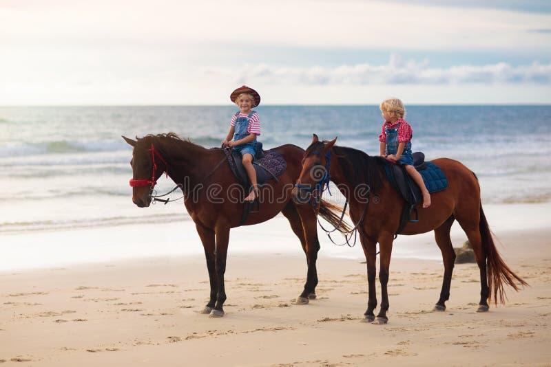 孩子在海滩的骑乘马 孩子骑马 库存照片