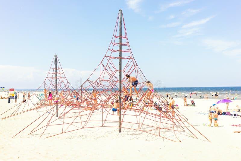 孩子在海滩的夏天由海攀登绳索 库存图片