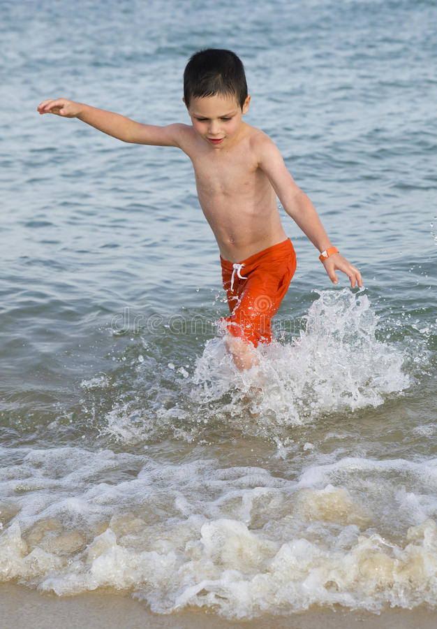 孩子在海滩的水中 库存图片