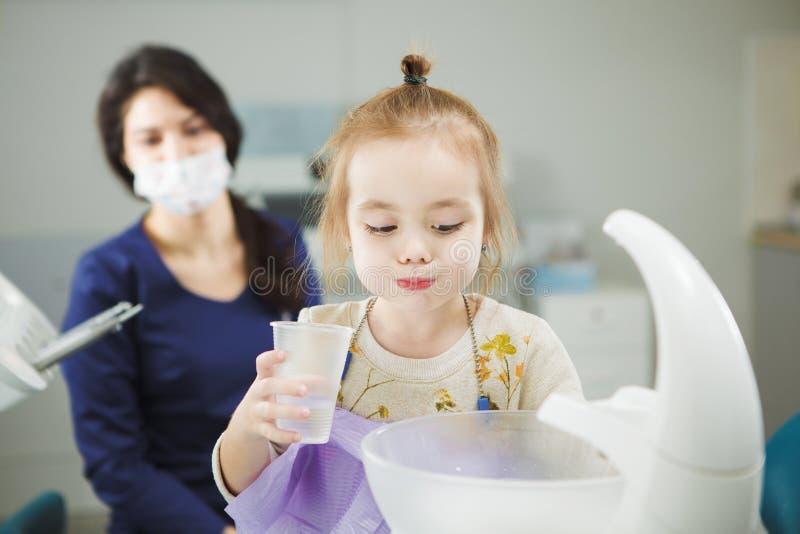 孩子在牙医椅子漂洗嘴并且坐 库存图片