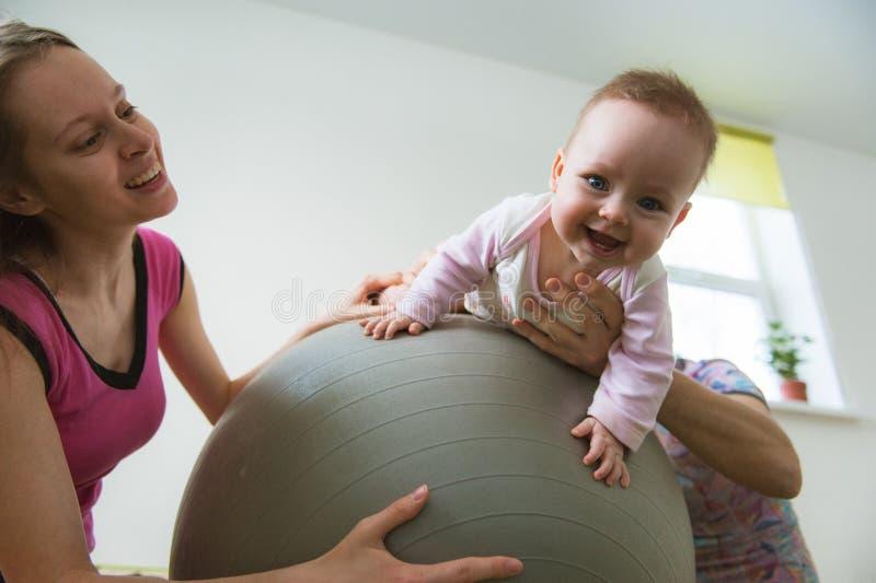 孩子在球跳在父母帮助下  库存照片