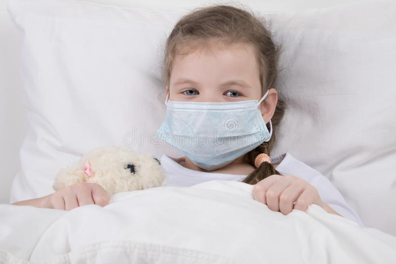 孩子在白色床上,在他的面孔戴着一个医疗面具,反对流感 免版税库存照片