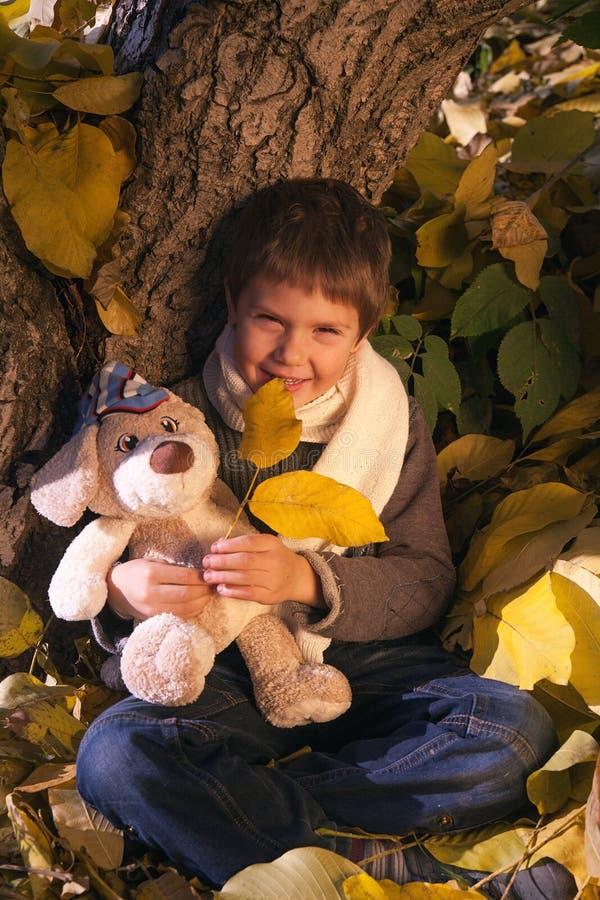 孩子在秋天庭院里 免版税库存图片